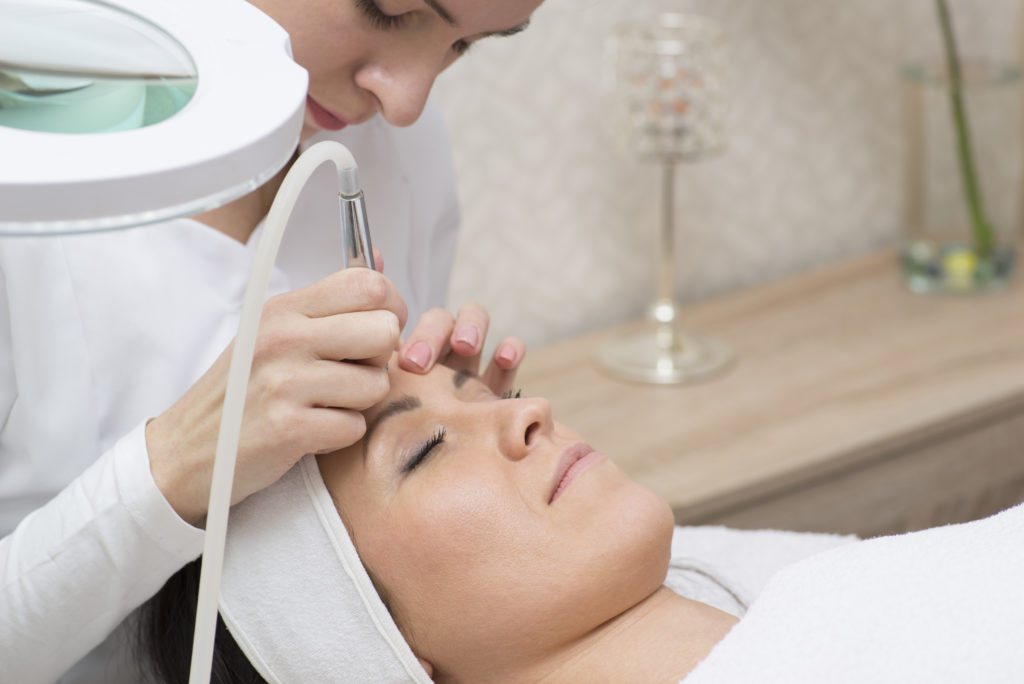 Image of Close-up top-view side-view portrait of a young woman with a towel on her head lying on a table with closed eyes getting a laser skin treatment in healthy beauty spa salon
